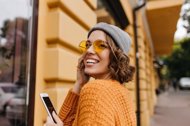 Raffinata donna dai capelli corti in occhiali da sole guardando sopra la sua spalla mentre posa per strada
