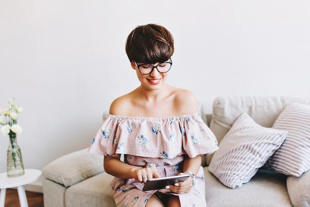 쿠션 사이에 앉아있는 동안 태블릿으로 작업하는 최신 유행 안경에 세련된 웃는 소녀