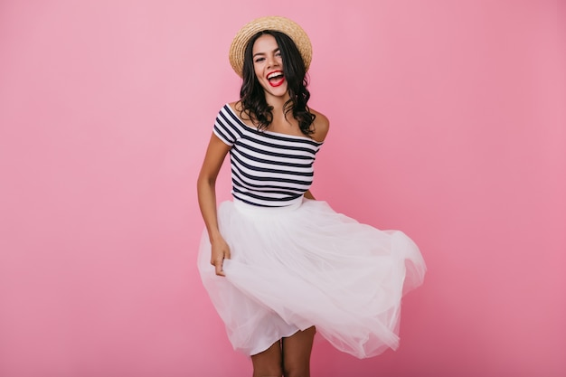 スカートで遊んでいるウェーブのかかった髪の洗練された日焼けした女の子。麦わら帽子のスリムな興奮した女性の屋内ショット。