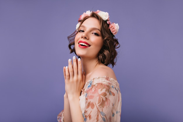 Refined white female model in romantic outfit laughing. debonair short-haired girl with flowers on her head smiling.