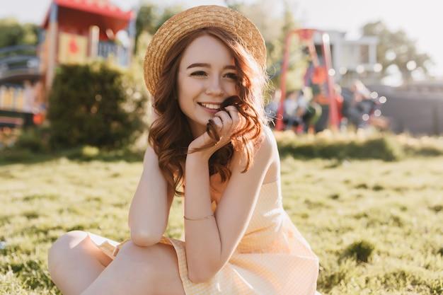 晴れた日に草の上に座っている洗練された白人の女の子。夏に芝生の上でポーズをとって笑っている生姜巻き毛の若い女性。