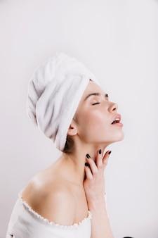 Утонченная женщина, наслаждаясь утренней рутиной. портрет дамы в полотенце на изолированной стене.