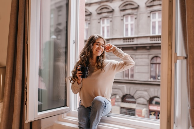 창에서 도시 전망을 즐기는 트렌디 한 셔츠에 세련된 여성