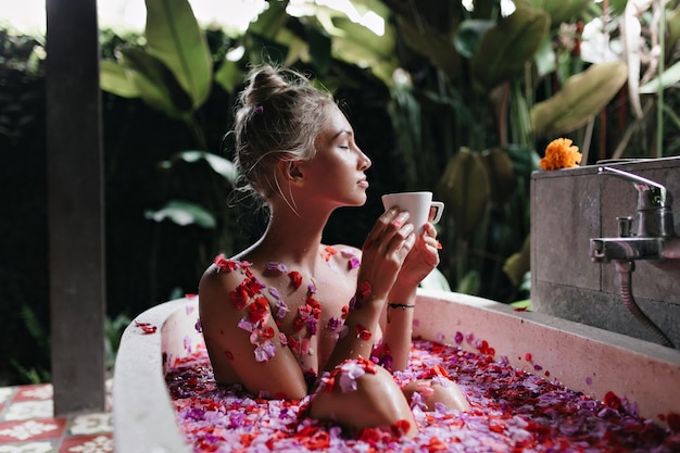 自然の背景に風呂に座っている洗練された女性。スパでリラックスしてお茶を飲む素敵な白人女性。