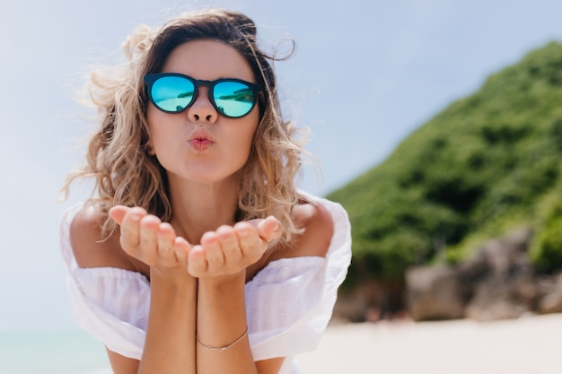 검게 그을린 피부가 자연에 키스하는 얼굴 표정으로 포즈를 취하는 세련된 여자. 화창한 아침에 해변에 물결 모양의 머리 서와 매혹적인 여성 모드의 야외 촬영.