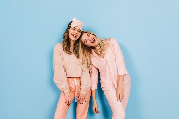 一緒にポーズをとるピンクのパジャマで洗練された女性