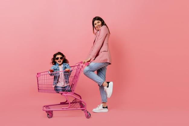 Утонченная молодая мать с ребенком позирует после покупок. вид в полный рост семьи с магазинной тележкой.