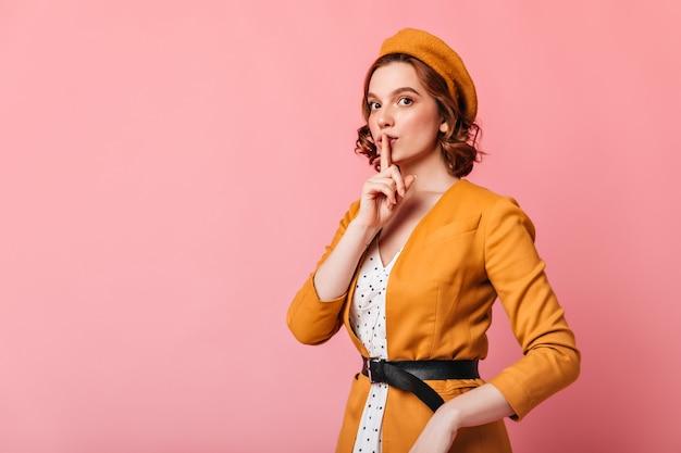 Raffinata giovane donna in berretto che mostra un segno segreto. modello femminile abbastanza francese che tocca le labbra con il dito.
