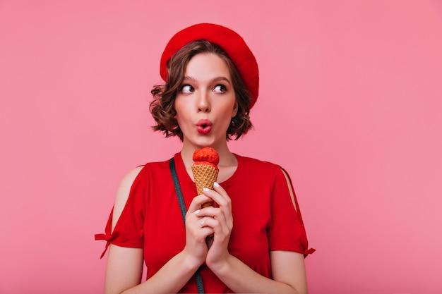 Giovane donna raffinata in berretto affascinante che mangia il gelato. ragazza emotiva in abito rosso godendo il dessert.