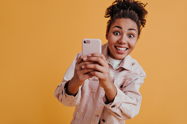 Refined young woman holding smartphone