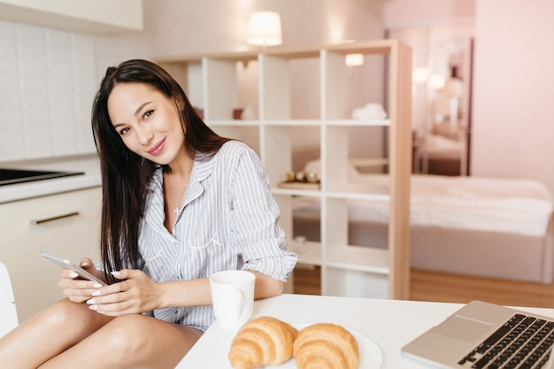 Refined young woman sits at the table with laptop and croissants on it and smiling