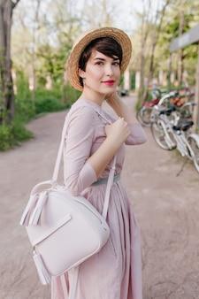 トレンディな白いバックパックを背負って、路上でポーズをとる短い髪と薄い肌を持つ洗練された若い女性