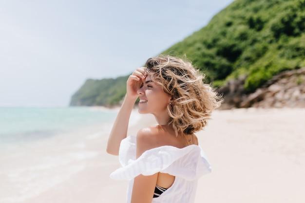 바다를보고 짧은 빛 머리를 가진 세련 된 젊은 여자. 해변 주위를 산책하는 사랑스러운 검게 여자의 야외 초상화.