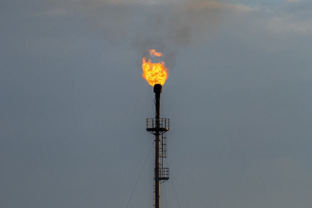 Refinery fire gas torch against the gray sky