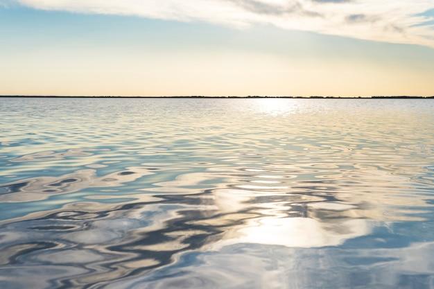 바닷물에 반사된 태양 광선. 별의 형태로 물에 눈부심. 자연 추상 바다 물 배경입니다.
