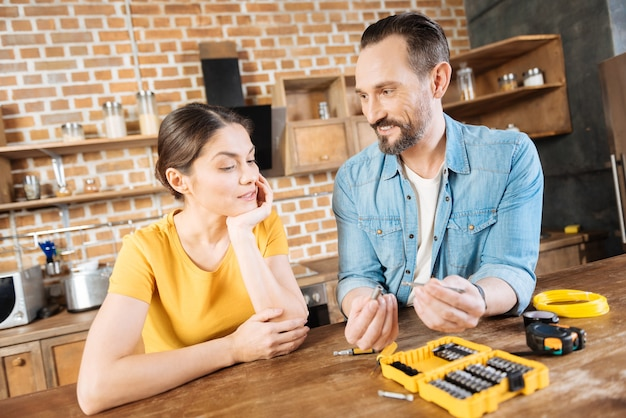 Reflecting happy cheerful couple deciding what nails take while talking