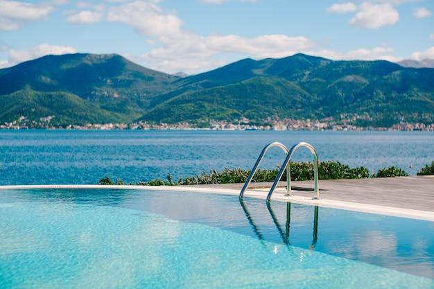 プールの滑らかな水に山の海と空を反映