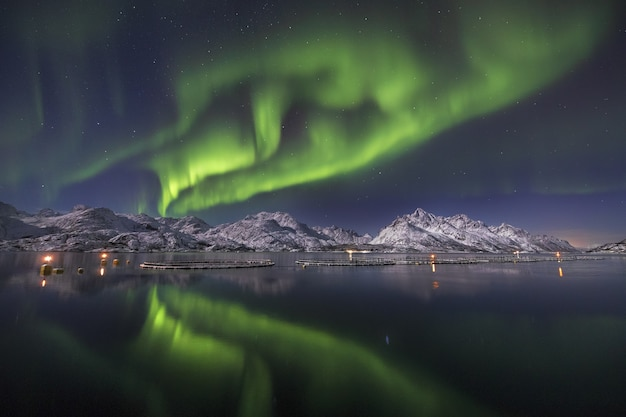 Reflection of the beautiful northern lights in he water surrounded by snow covered mountains