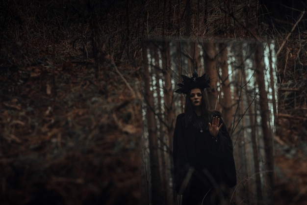 Reflection of a black terrible witch in a mirror in a dark forest