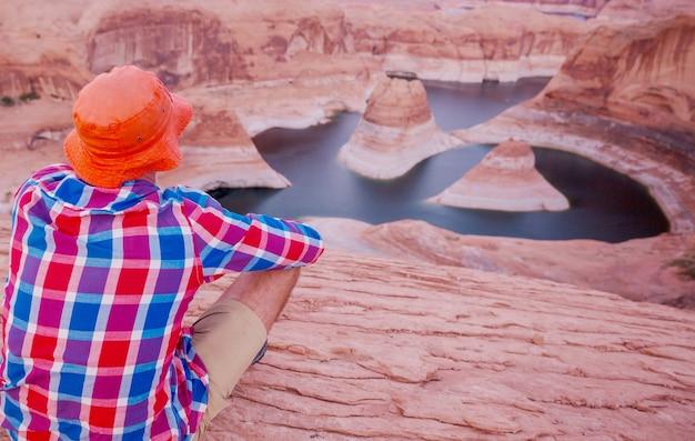 米国ユタ州パウエル湖のリフレクションキャニオン。感動的なハイキングシーン-美しい夕日のポイントで休んでいる男。
