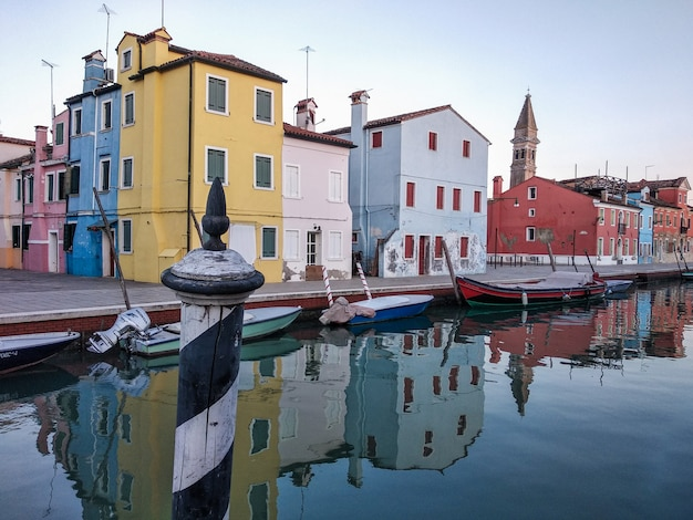 Reflection in the channel of the typical colorful houses of the island of burano, venice, italy.