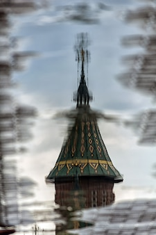 Reflection of a church tower in a puddle on the street