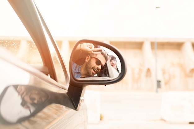 Reflection of couple in car side mirror