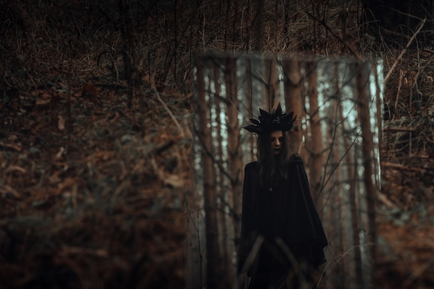 Reflection of a dark frightening witch in a mirror in a gloomy forest