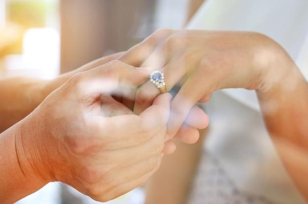結婚式のリングで花嫁と新郎の窓ガラスからの反射