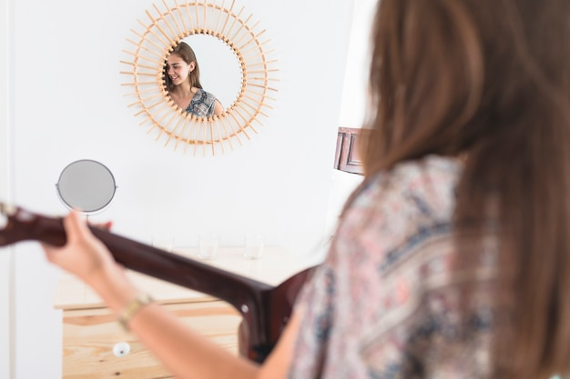 Reflection of happy teenage girl in mirror playing guitar