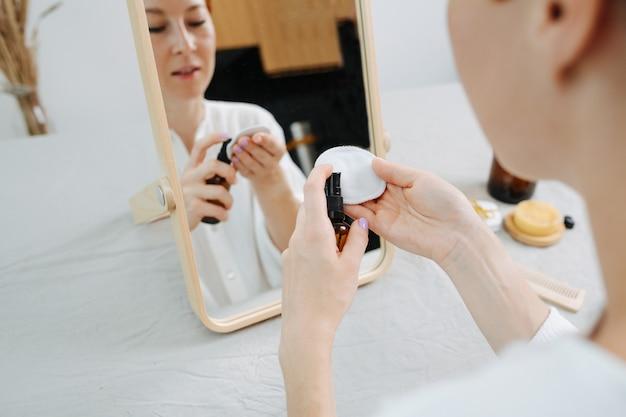 Отражение изображения женщины, сидящей перед зеркалом, применяющей мицеллярную воду. использование экологически чистых продуктов и вещей.