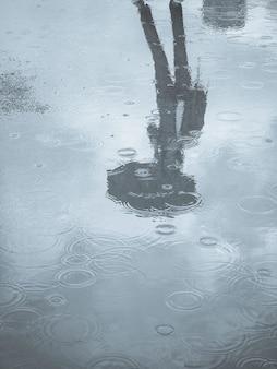 傘を持つ女性の水たまりのシルエットの反射。水たまりに傘を持つ男のシルエットの反射。気候変動の概念。