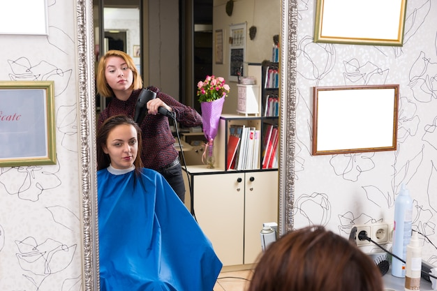 ヘアサロンで青いスモックを身に着けているブルネットのクライアントの若いブロンドのスタイリストブロー乾燥髪の大きな鏡の反射