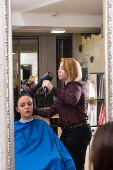 ブロードライヤーを使用してスモークを着てサロンの椅子に座っている女性のブルネットクライアントの髪を乾かす金髪スタイリストの鏡の反射
