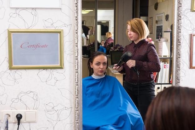壁に掛かっている教育資格証明書に囲まれたサロンで熱風ブロードライヤーを使用してブロンドのスタイリストによって乾かされた濡れた髪を持っている若いブルネットの女性の鏡に映る