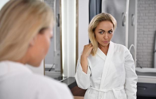 スパセンターの鏡の前に立って、自分を賞賛する美しい若い女性の鏡に映る