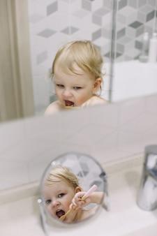 Отражение в зеркале маленькой забавной девочки, чистящей зубы