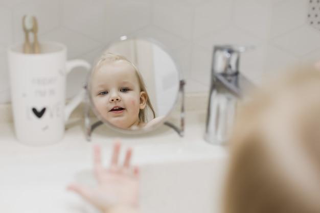 浴室で手と顔を洗う小さな面白い女の子の鏡に映る