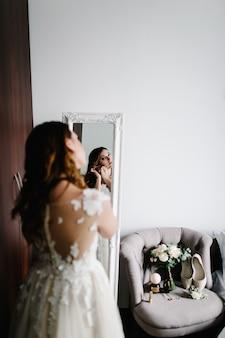 鏡の中の反射。白いドレスを着た花嫁は、鏡の近くの部屋で真珠のついた金のイヤリングを着ています。花嫁の装飾の手に。結婚式の朝。女性の背中を見てください。