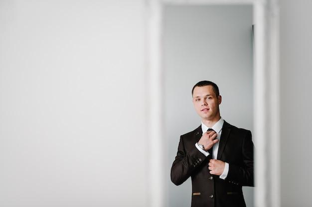 Отражение в зеркале, мужчина в костюме смотрит на себя и поправляет галстук на рубашке дома. концепция одежды. готовимся к деловой встрече.