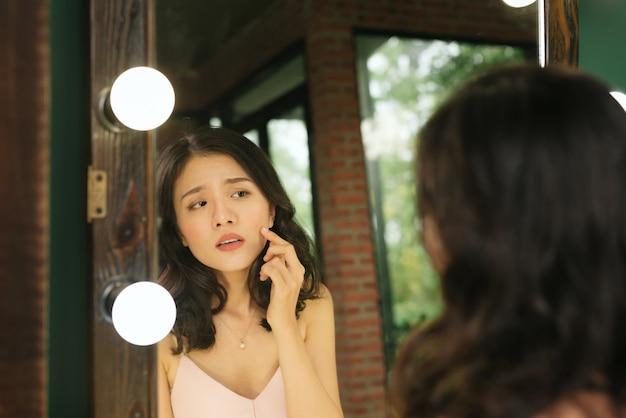 鏡の中の反射。女性は最初のしわに気づいて鏡を見る