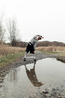 Reflection of male athlete in puddle exercising