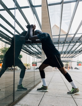 Reflection of male athlete stretching his muscle leaning on reflective glass