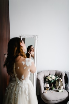 Reflection in the mirror. the bride in a white dress wears gold earrings with pearls in the room near the mirror. in the hands of bride decoration. wedding morning. a look on the back of the woman's.