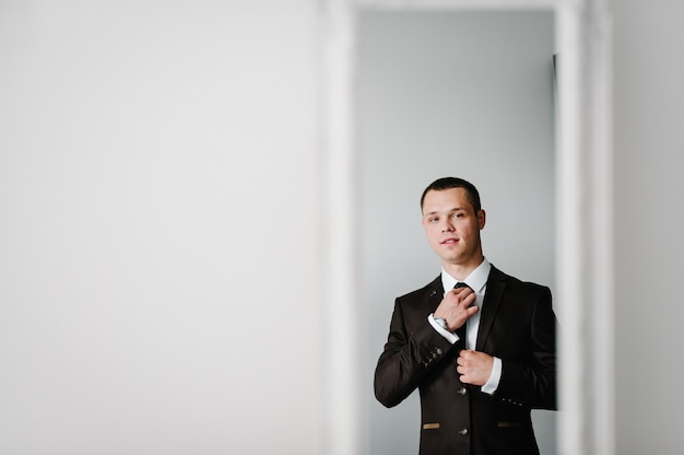 Reflection in the mirror, the man in a suit looks at on yourself and straightens tie on shirt at home. clothing concept. preparing for a business meeting.