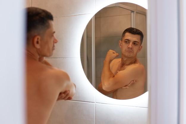 Riflessione nello specchio uomo fiero sicuro di sé con i capelli scuri e il corpo nudo, guardando i suoi bicipiti con espressione facciale soddisfatta, in posa in bagno.
