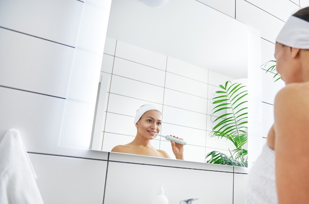 Reflection in the mirror of a young pretty and healthy woman brushing her teeth.