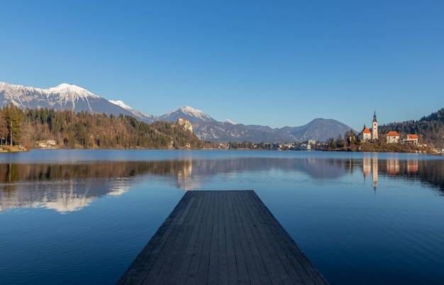 Reflection of the mountains and old buildings in the lake with a wooden pier in the foreground