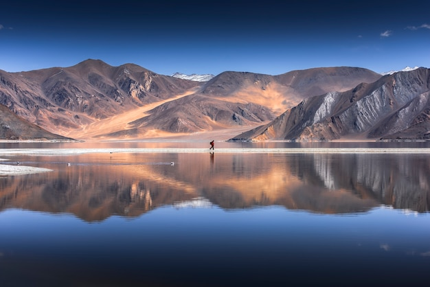 Reflection of mountains on pangong lake with blue sky background