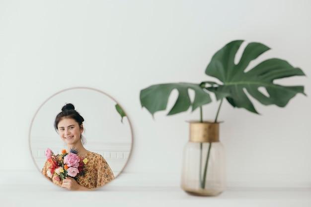 꽃과 함께 아름 다운 젊은 여자의 반영
